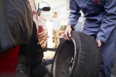 Mechanic replacing tire in auto repair shop Stock Photos