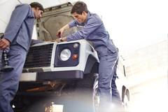 Mechanics working on engine in auto repair shop - stock photo