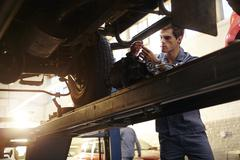 Mechanic working under car in auto repair shop Stock Photos