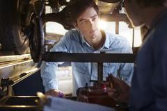 Mechanic and customer talking under car in auto repair shop - stock photo