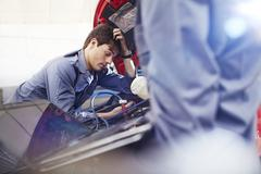 Frustrated mechanic looking down at engine in auto repair shop Stock Photos