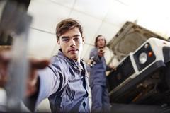 Mechanic reaching for tool below car in auto repair shop Stock Photos