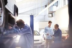 Mechanic speaking with customer in auto repair shop Stock Photos