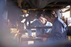 Mechanic and customer under car in auto repair shop Stock Photos
