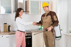 Happy Woman And Young Pest Control Worker Shaking Hands To Each Other In Kitc - stock photo
