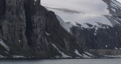 Bird Cliff with Snow Field and Spires near Ocean Stock Footage