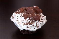 Delicious chocolate cupcake with hear-shaped sprinkles - stock photo