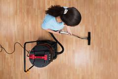 High Angle View Of Young Woman Cleaning Floor With Vacuum Cleaner Stock Photos