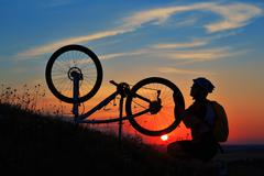 Silhouette of man cyclist repairing a bike  against sunset Stock Photos
