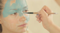 Application of blue paint on the model's face in certain areas by makeup artist Stock Footage