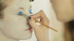 Visagist applying blue eye shadow with brush Stock Footage