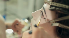 Stock Video Footage of Visagist draws arrows on the model's face, the image of the heroine of the