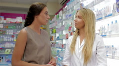 Beautiful girl pharmacist consulting a customer Stock Footage