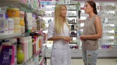 Beautiful girl pharmacist consulting a customer - stock footage