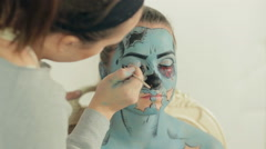 Application of greasepaint on the model's face, the image of zombie Stock Footage