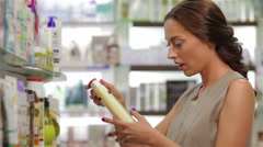 Beautiful young woman looking for proper shampoo - stock footage