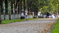 Young people sit on a bench in the park. Stock Footage