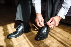 Business man tying shoe laces on the floor - stock photo