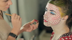 Visagist applies the red dots on the model's face, the image of the heroine of Stock Footage