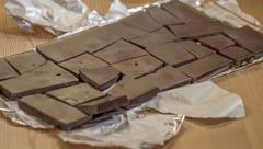 Unwrap chocolate bar, breaking into pieces, eating, discard wrapper, stop motion Stock Footage