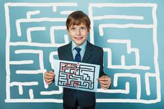 Stock Photo of a boy of twelve European appearance in a suit holding a blank sh
