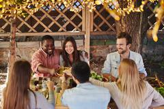 Guests by festive table - stock photo