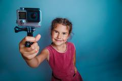 Teen girl child seven years, European appearance brunette holding action camera Stock Photos