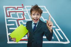 a boy of twelve European appearance in a suit holding a blank sh - stock photo