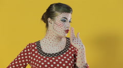 Funny girl made up as comics heroine shows different emotions on a bright yellow - stock footage