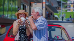 An elderly couple enjoying themselves eating doughnuts Stock Footage