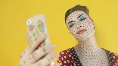 Women make up as a comic book heroine makes selfie on phone in studio Stock Footage