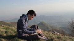 Man reads the book in the mountains Stock Footage