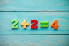 Mathematical addition on a wooden surface - stock photo