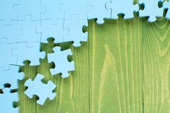 Puzzle on green wooden background Stock Photos