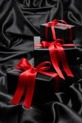 Stock Photo of Black gift boxe with red satin ribbons and bows, over black satin