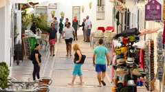 Tourists walking in a typical street village andalusian at sunset Stock Footage