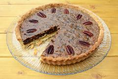 Pecan pie on a plate with one slice taken Stock Photos