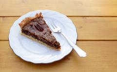 Slice of pecan pie on a china plate with a fork Stock Photos