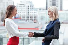 Cheerful young businesswomen are congratulating each other Stock Photos