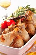 Roasted chicken drumsticks in a casserole dish - stock photo