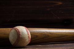 A wooden baseball bat and ball on a wooden background Kuvituskuvat