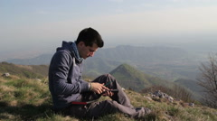 Boy writes in his diary, alone on the mountain Stock Footage