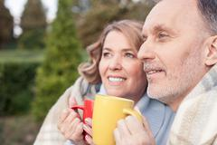 Pretty mature husband and wife are warming with hot drink Stock Photos