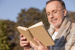 Cheerful old male pensioner is resting in the nature Stock Photos