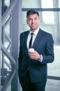 Attractive young man in suit is enjoying hot drink Stock Photos