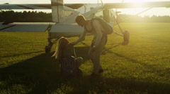 Man is Helping to Girl to Put on Parachute Before Flight - stock footage