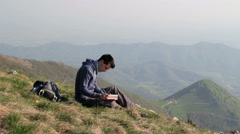 Person alone writes in his diary on top of the mountain Stock Footage