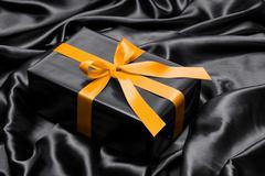 Black gift box with yellow satin ribbon and bow - stock photo