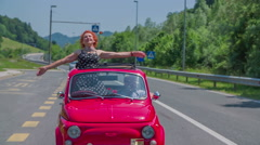An older lady stretches her arms and plays with her hair during a car ride Stock Footage