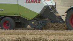 Baler at work on wheat straw. - stock footage